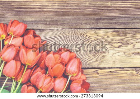 Bouquet of delicate fresh red tulips lying on a wood textured background with wood grain pattern and copyspace for a Valentines Day card - stock photo