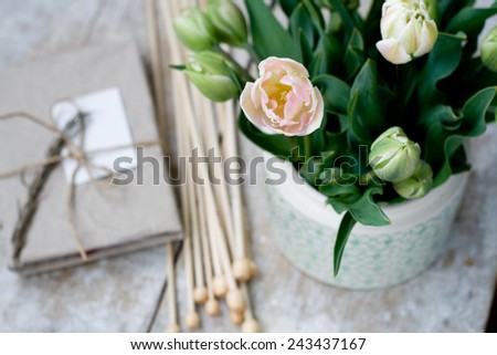 Bouquet of delicate pink tulips and needles for knitting on a wooden background