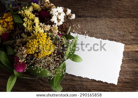 Bouquet of dried flowers and empty paper card on a wooden background. - stock photo