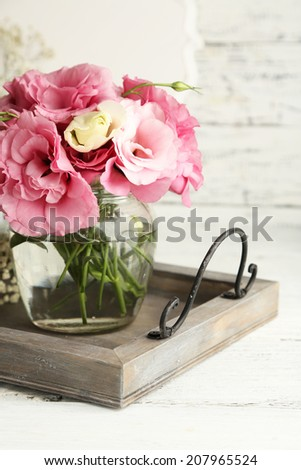 Bouquet of eustoma flowers in vase on wooden background - stock photo