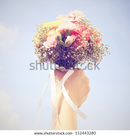 Bouquet of flower in hand and blue sky with retro filter effect - stock photo