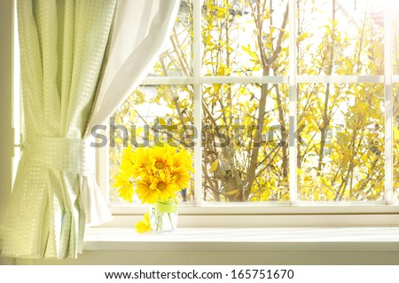 bouquet of flower on a windowsill in a fall - stock photo