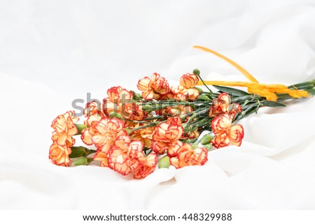 Bouquet of flowers. Bunch of carnation bloom. Orange yellow blooming blossom on the white fabric texture background. Card for birthday, anniversary, wedding or celebration. - stock photo