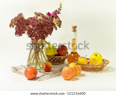 Bouquet of flowers in a glass jar with apples on a white background - stock photo