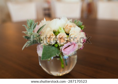 bouquet of flowers in a vase on a brown wood background