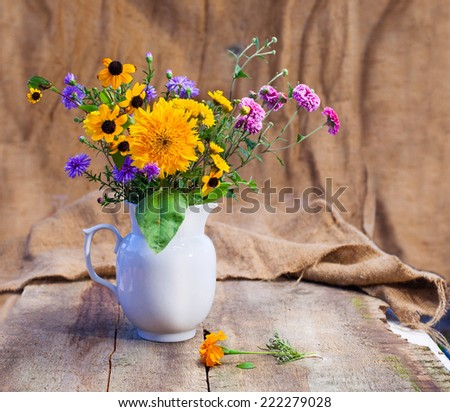 bouquet of flowers in a white vase on a wooden table canvas background - stock photo