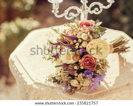 Bouquet of flowers lying on a stone table with a candlestick outdoors.