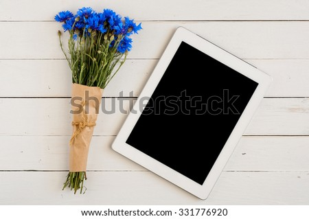 bouquet of flowers on a white wooden table with a tablet computer with a blank screen. Bouquet of wild flowers (centaurea). Copy space. Free space for text. Top view - stock photo