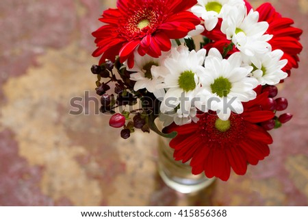 Bouquet of flowers with a red flower gerbera daisy on a wooden vintage background, top view. - stock photo
