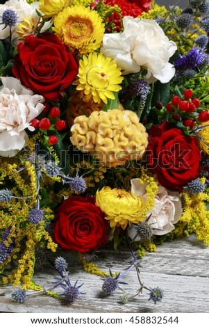 Bouquet of flowers with red roses, yellow celosias and white carnations. - stock photo