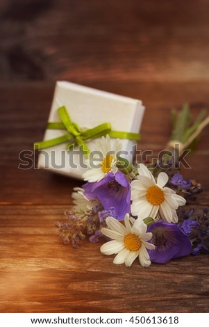 Bouquet of flowers with small gift on wooden background