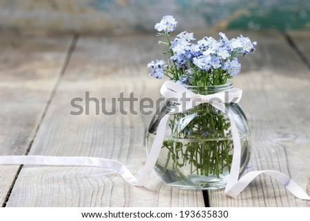 Bouquet of forget-me-not flowers in glass vase - stock photo