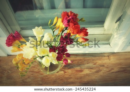 Bouquet of freesias near the window. High angle view - stock photo