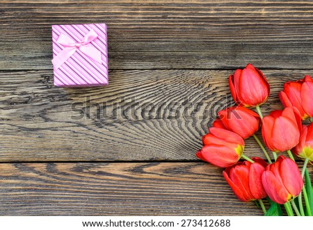 Bouquet of fresh colorful red tulips with a decorative gift lying on a rustic wooden background symbolic of an anniversary, Valentines Day and love, overhead view - stock photo