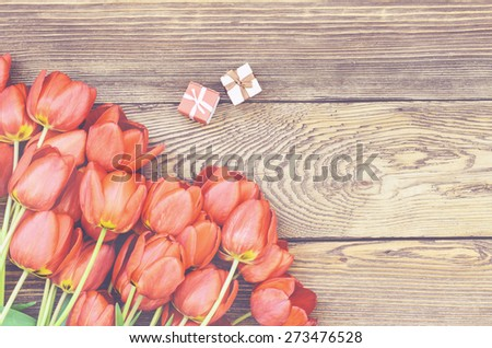 Bouquet of Fresh Orange Tulip Flowers on Top of Wooden Table with Two Little Gift Boxes, Captured in High Angle View. - stock photo