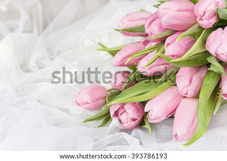 Bouquet of fresh pink tulips flowers covered with dew drops are on lacy textile close-up