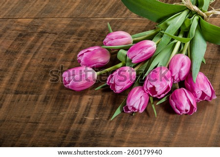 Bouquet of fresh pink tulips on a wooden table - stock photo