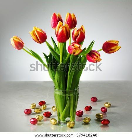 bouquet of fresh tulips in a glass vase  and small red yellow chocolate easter eggs on the table, cheerful spring decoration against a gray background - stock photo