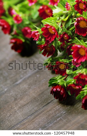 Bouquet of fresh wild red flowers on old wooden table - stock photo