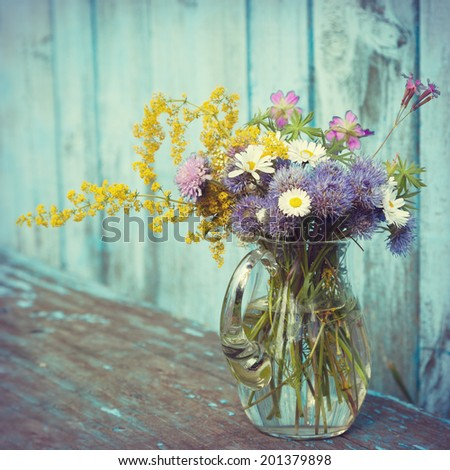bouquet of garden flowers and healing herbs in glass jug on old wooden bench - stock photo