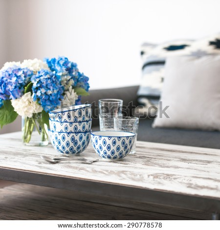 Bouquet of hortensia flowers and glass bowls on modern wooden coffee table and cozy sofa with pillows. Living room interior and home decor concept - stock photo