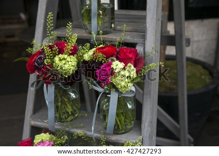 Bouquet of hydrangea, carnations and hydrangeas in a glass jar on the stairs