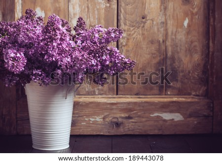 Bouquet of lilac flowers in a pot on a background of vintage wooden board, home decor in a rustic style - stock photo