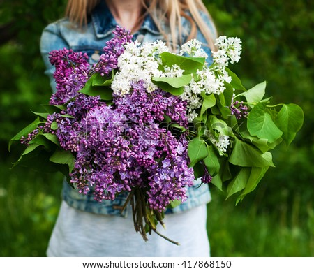 bouquet of lilac flowers in girl's hand - stock photo