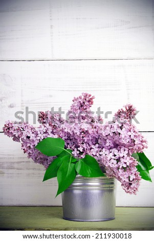 bouquet of lilac flowers on white wooden background - retro filter - stock photo