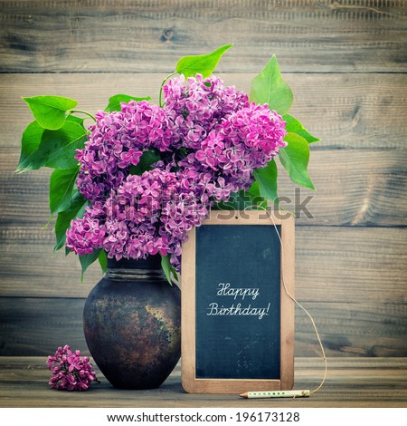 bouquet of lilac flowers on wooden background. blackboard with sample text Happy Birthday! retro style toned picture - stock photo