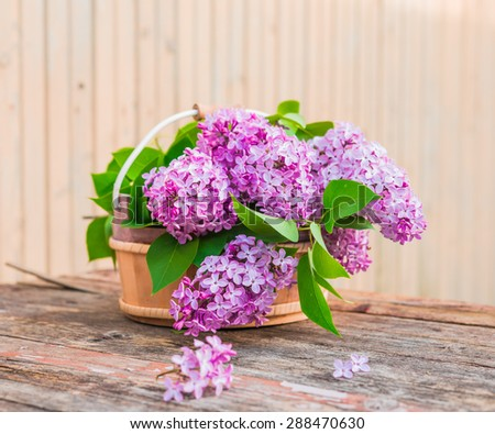 Bouquet of lilac flowers on wooden background. Vintage floral background.
