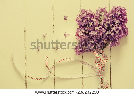 Bouquet of lilac spring flowers on light shabby chic background  - stock photo