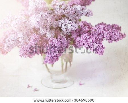 Bouquet of lilacs in a glass vase. Lilac flowers in vintage style. - stock photo