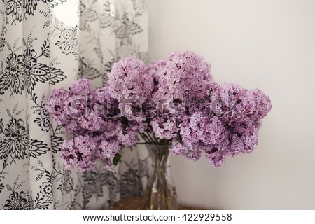 Bouquet of lilacs in a glass vase. Lilac flowers in vintage style against white background. - stock photo