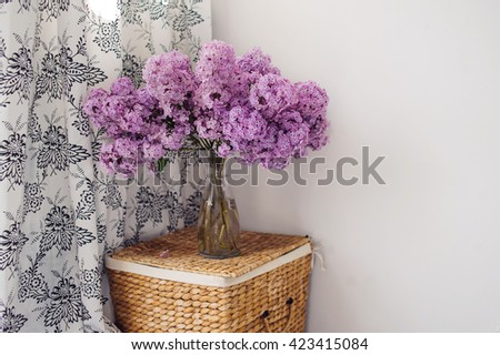 Bouquet of lilacs in a glass vase. Lilac flowers in vintage style against white background.