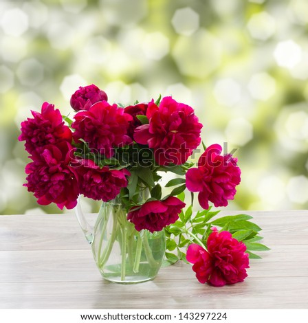 bouquet of mauve peonies on a garden table - stock photo