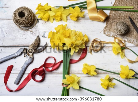 Bouquet of narcissus and gardening tools on rustic wooden table - stock photo