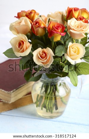 Bouquet of orange roses in vase on blue wooden background