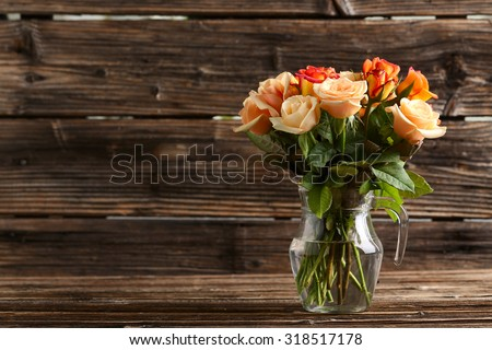 Bouquet of orange roses in vase on brown wooden background - stock photo