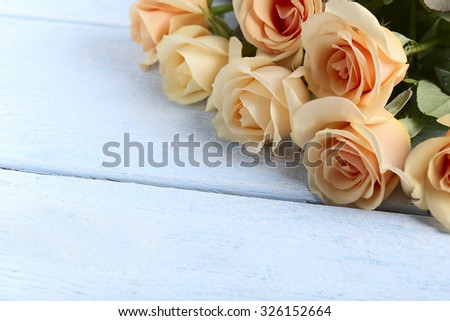 Bouquet of orange roses on blue wooden background - stock photo