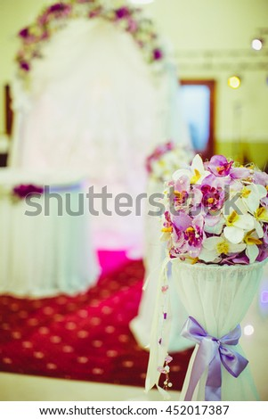 Bouquet of orchids stands on the little round table in the front of wedding altar