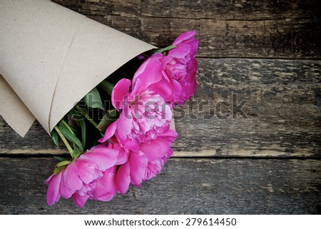 Bouquet of peonies on the old wooden background