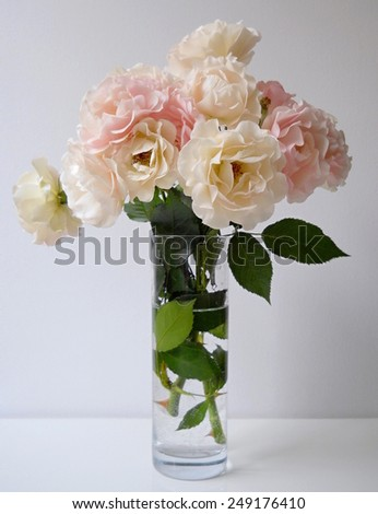 Bouquet of pink and creamy colored roses in a glass vase.