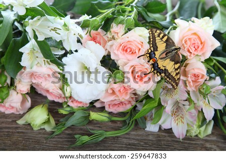 Bouquet of pink and white flowers and butterfly on a wooden background