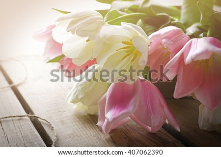 Bouquet of pink and white tulips on wooden background