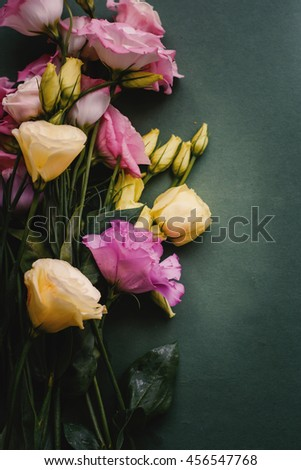 Bouquet of pink and yellow lisianthus on green background. - stock photo