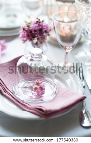 Bouquet of pink flowers in a glass bell jar on a festive wedding decorated table, a bright summer table decor. - stock photo