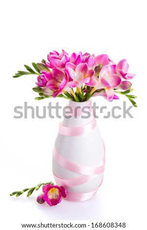 Bouquet of pink flowers in a white vase decorated with ribbon - stock photo