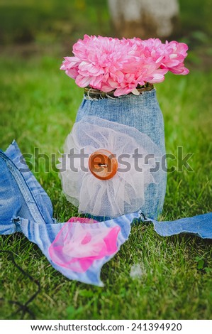 Bouquet of pink flowers in the denim vase on grass outdoors together with denim banner flags - stock photo