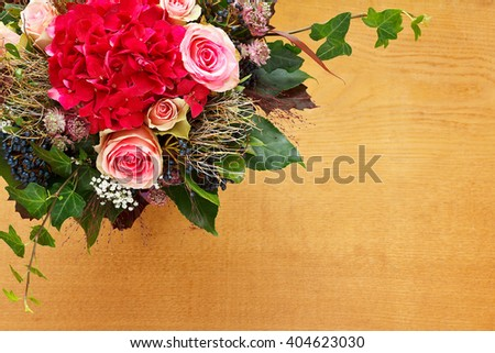 Bouquet of pink rose and red hortensia flowers with ivy on a light wooden background, top view, copy space, copyspace,  - stock photo